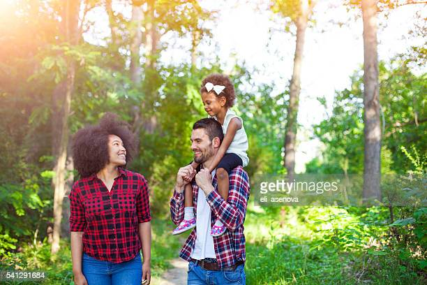 Happy family walking along a path in the woods