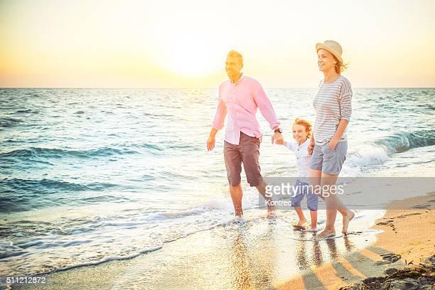 Happy family walking along a sandy beach
