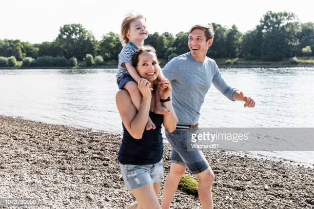 happy family walking at the riverside on a beautiful summer day - trois personnes photos et images de collection