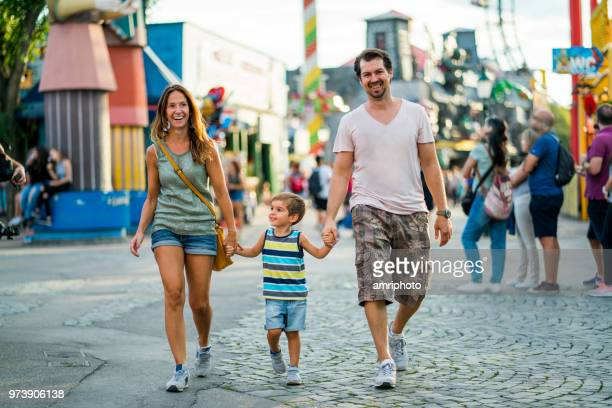 happy family walking hand in hand - amusement park stock pictures, royalty-free photos & images