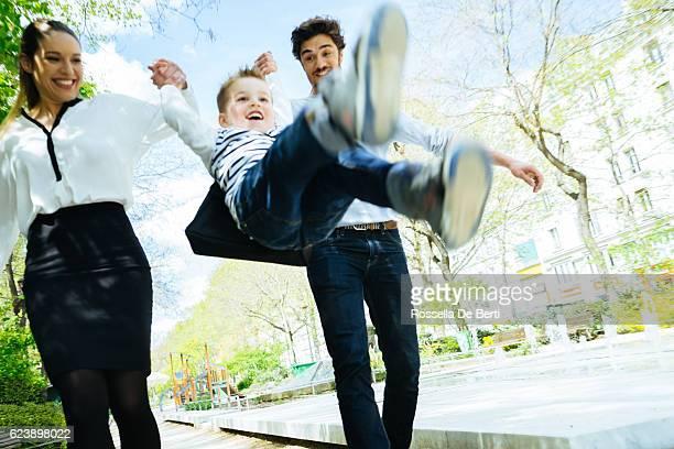 Heureuse famille marche dans le parc en fils à l'école