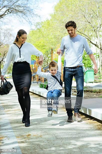 Glückliche Familie Fuß im Park mit Sohn zur Schule