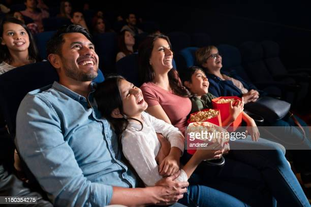 happy family watching a comedy film at the cinema - industria cinematografica foto e immagini stock
