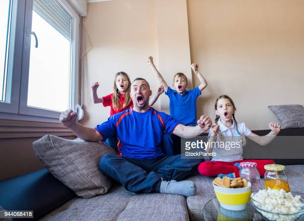 Familia feliz mirando un partido de fútbol juntos