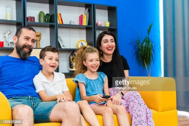 happy  family watching television together - film and television screening bildbanksfoton och bilder