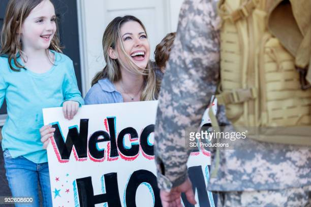 happy family welcomes home army dad - military spouse stock pictures, royalty-free photos & images
