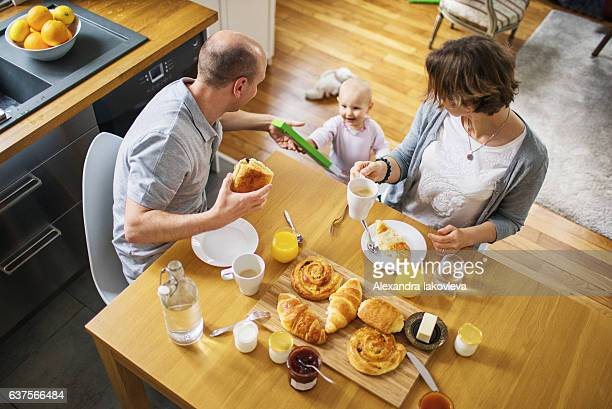 Happy family with a child eating french breakfast at home