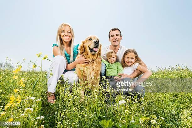 Familia feliz con golden retriever.