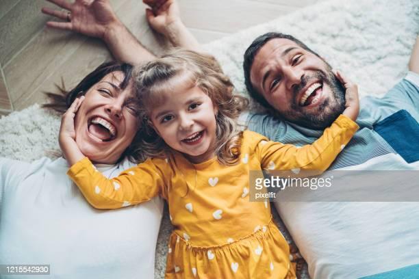 glückliche familie mit einem kleinen mädchen auf dem boden liegen - familie mit einem kind stock-fotos und bilder