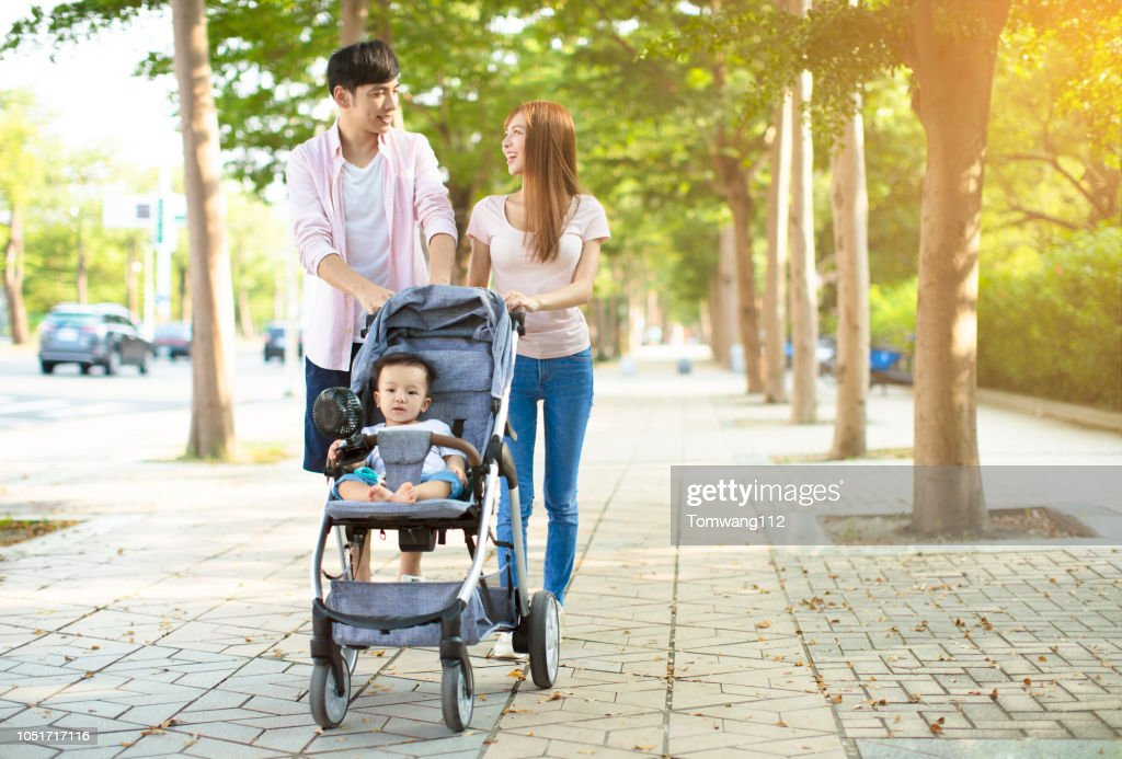 happy family with baby carriage walking in the park : Stock Photo