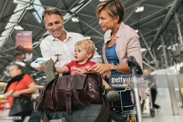 happy family with baggage cart at the airport - 公共の建物 ストックフォトと画像