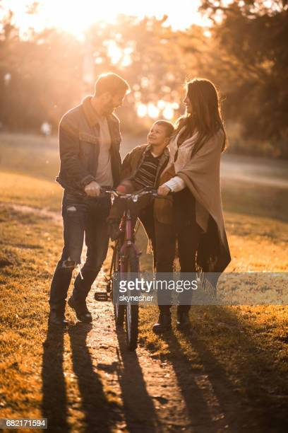Happy family with bicycle enjoying in autumn day at sunset.