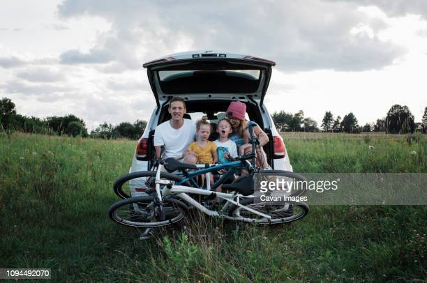 happy family with bicycles sitting on car trunk amidst grassy field against cloudy sky - four people in car stock pictures, royalty-free photos & images