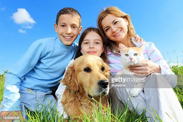 Glückliche Familie mit Katze und Hund Blick in die Kamera.