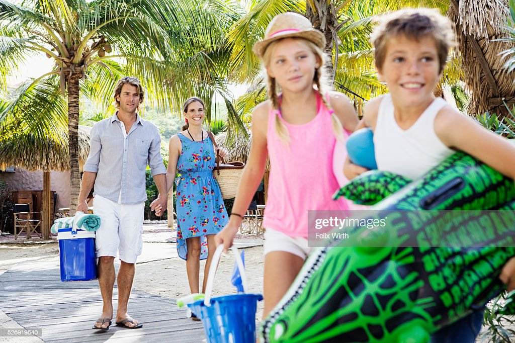 Happy family with children (10-12) on beach : Stock Photo