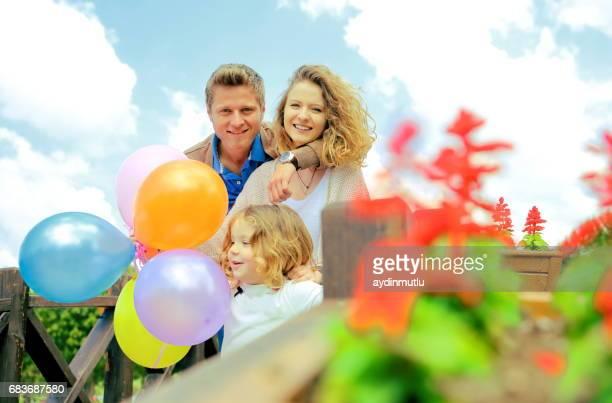 glückliche familie mit bunten luftballons - kindertag stock-fotos und bilder