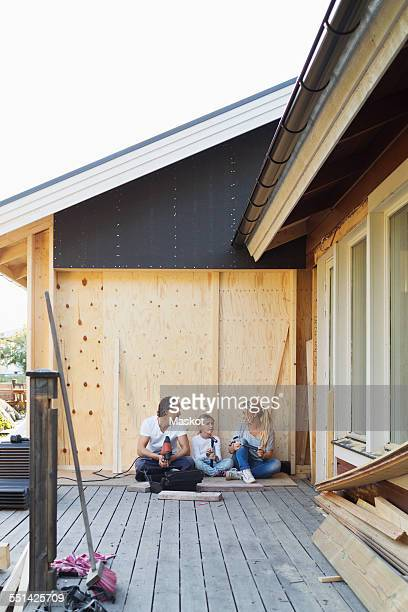 Happy family with construction tools sitting outside house
