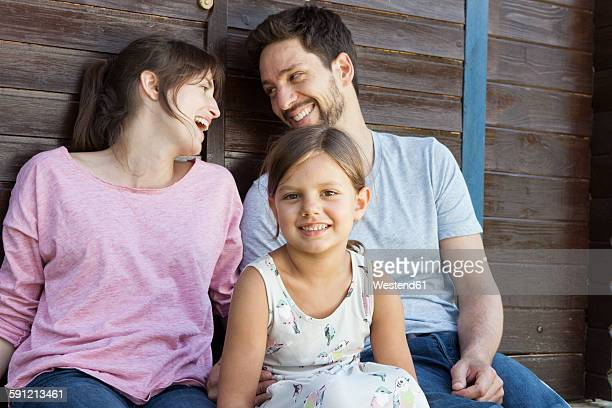 Happy family with daughter at garden shed