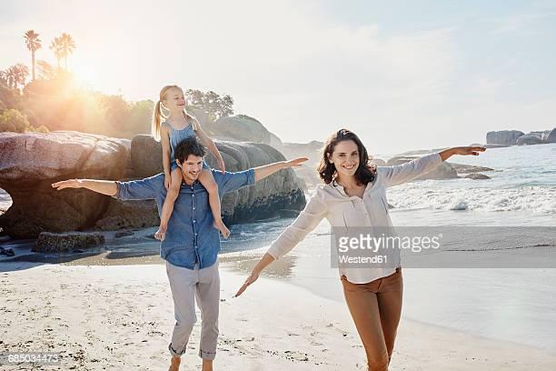 happy family with daughter on the beach - ausgestreckte arme stock-fotos und bilder