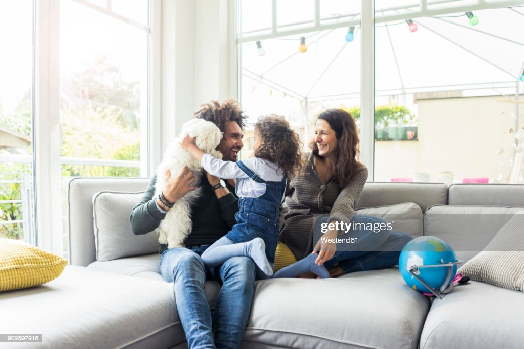 Happy family with dog sitting together in cozy living room : Stock Photo