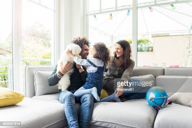 happy family with dog sitting together in cozy living room - biparental fotografías e imágenes de stock