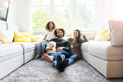 Happy family with dog sitting together in cozy living room - gettyimageskorea