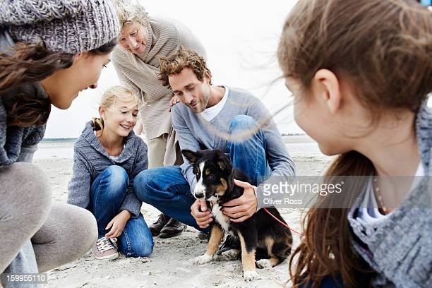 Happy family with grandmother and dog on the beach