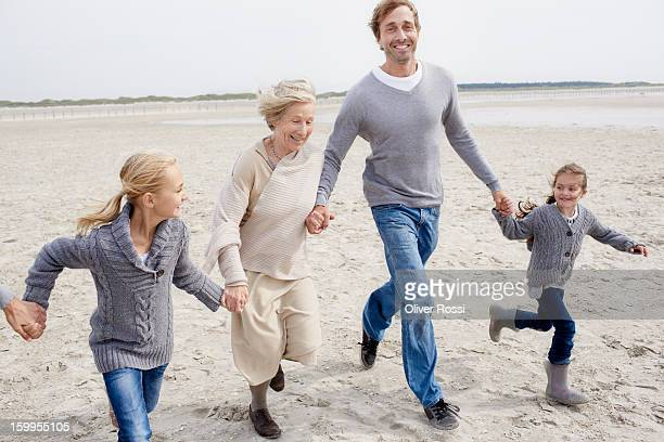 Happy family with grandmother running on the beach