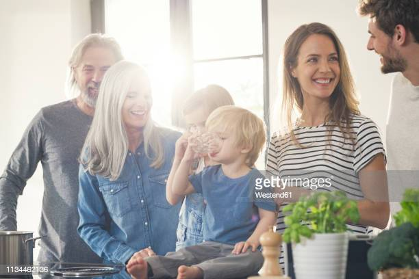 happy family with grandparents and children standing in the kitchen - family reunion stock pictures, royalty-free photos & images