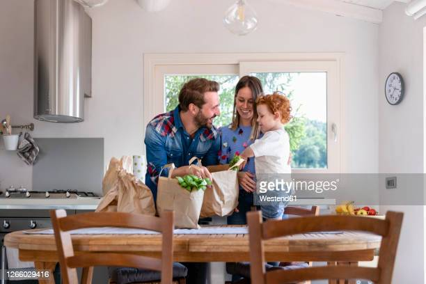 happy family with groceries bag at dining table in kitchen - three quarter length foto e immagini stock
