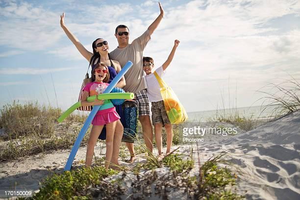 Família feliz com as mãos levantadas em pé na praia