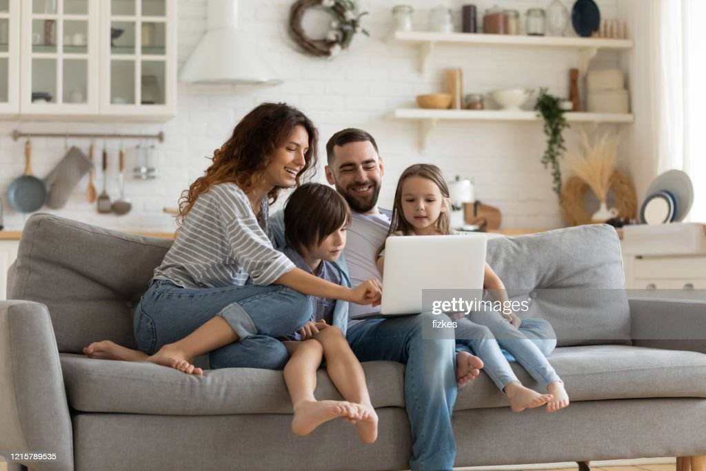 Happy family with kids sit on couch using laptop : Stock Photo