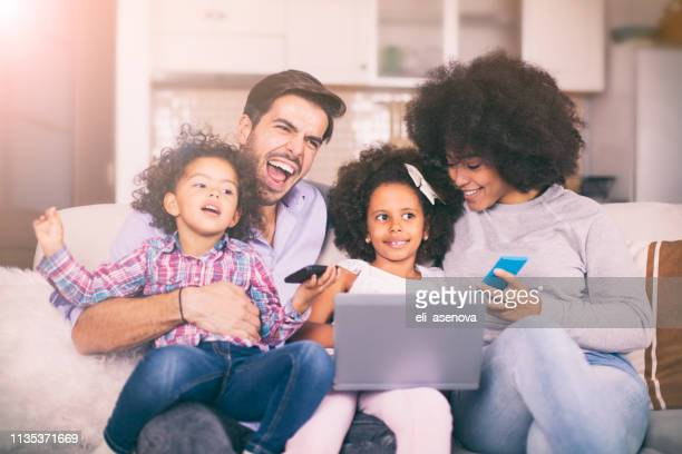 happy family with little kids enjoying using laptop computer together - white wife black baby stock photos and pictures