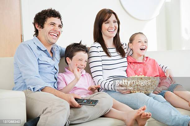 Happy family with popcorn watching TV on sofa