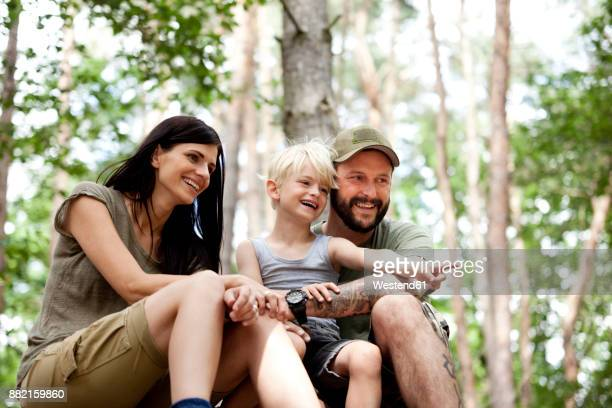 Happy family with son sitting in forest
