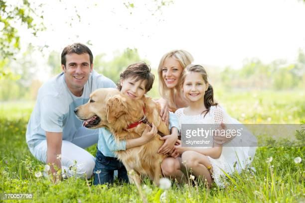 Familia feliz con su perro en el parque.