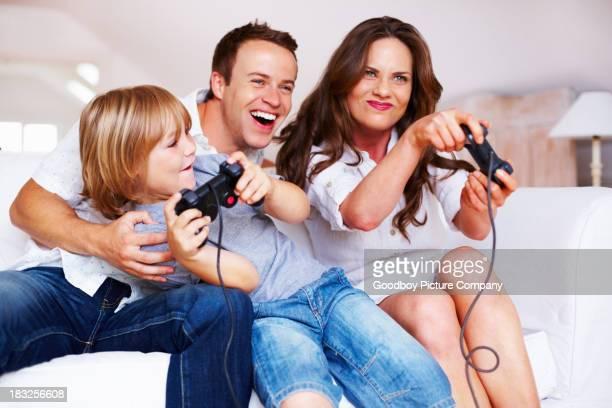 Famille heureuse avec les fils jouant des jeux vidéo à la maison