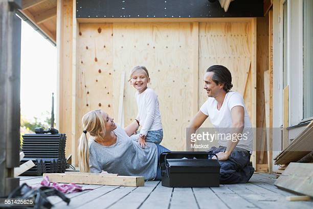 happy family with toolbox sitting outside house - familie mit einem kind stock-fotos und bilder