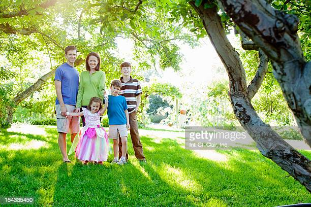 Happy family with tree children (4-5, 6-7, 12-13) in garden