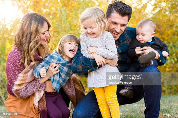 happy family with tree children (6-11 months, 2-3, 4-5) playing in park - 6 11 months stock pictures, royalty-free photos & images