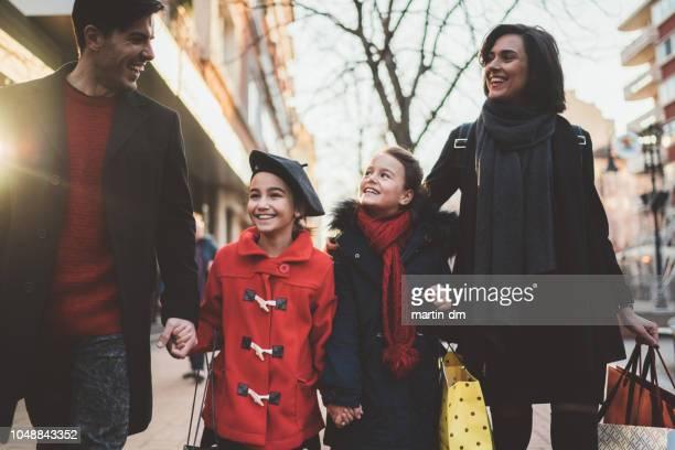 Glückliche Familie mit zwei Töchtern außerhalb am Weihnachts-shopping