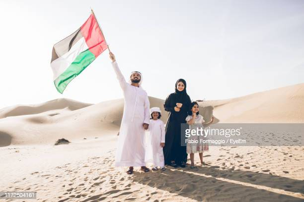 happy family with united arab emirates flag standing on sand dune - united arab emirates flag stock photos and pictures
