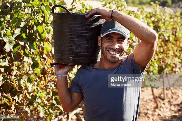 Happy farmer carrying container in vineyard