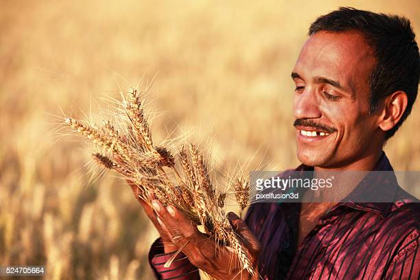 Happy farmer holding ear of wheat