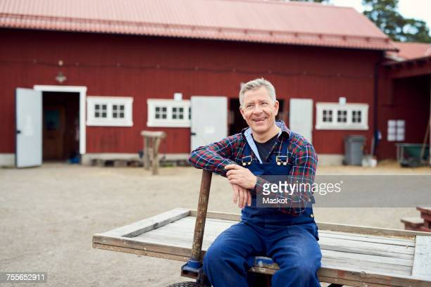 Happy farmer looking away while sitting on trailer against barn