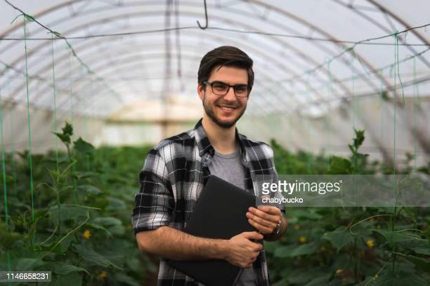 fazendeiro feliz com o portátil na estufa - técnico - fotografias e filmes do acervo