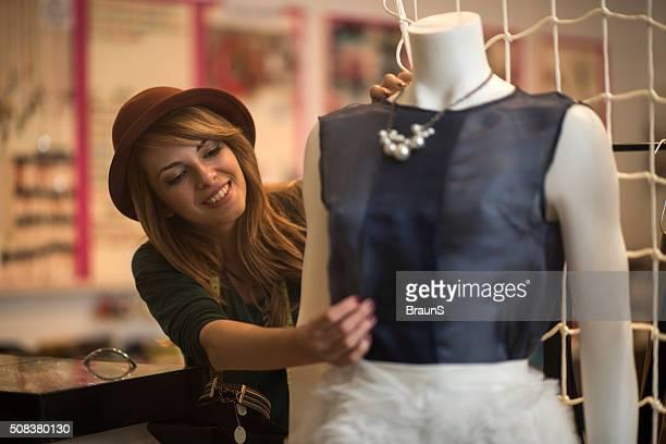 Happy fashion designer adjusting clothes on a mannequin.