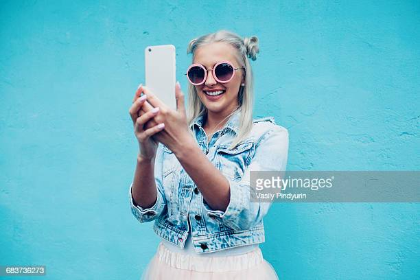 happy fashionable young woman talking selfie against blue wall - fotohandy stock-fotos und bilder