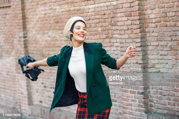 happy fashionable young woman wearing a beret and a green jacket at a brick wall - green coat stock pictures, royalty-free photos & images