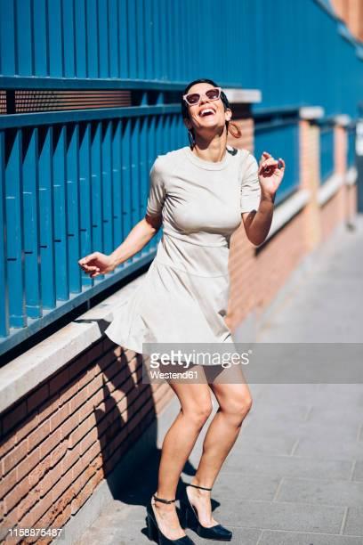 happy fashionable young woman wearing dress and sunglasses - solo una donna giovane foto e immagini stock